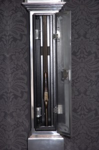 closeup of a guncase hidden inside a grandfather clock